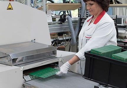 Frau nimmt Leiterplatte aus Maschine