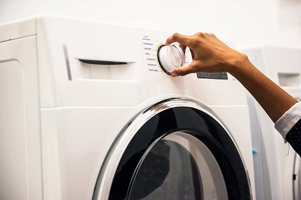 Frau bedient Waschmaschine