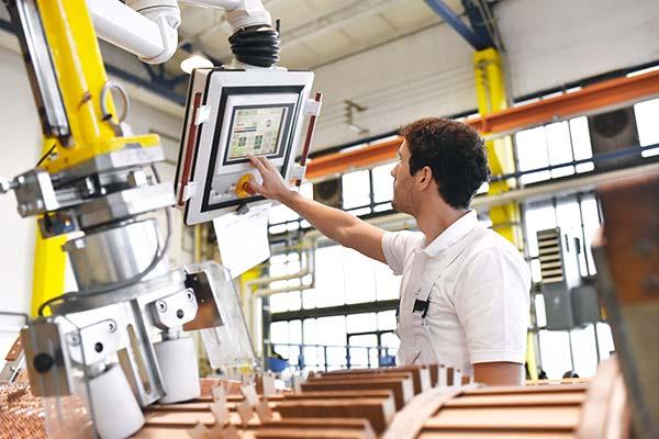 Mann bedient Industrieroboter