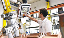 Mann tippt auf Monitor an Maschine