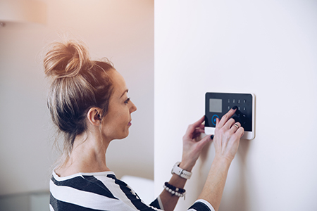 Frau betätigt Bedienpanel im Haus