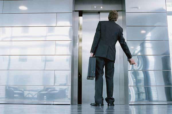 Mann steht vor Aufzug
